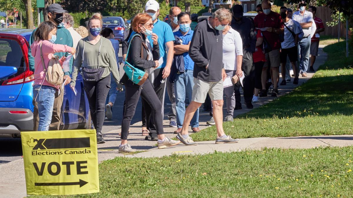 Una fila de personas espera para emitir su voto en Canadá.