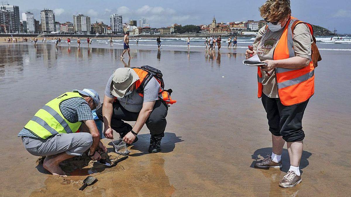 Técnicos del Incar, ayer, tomando muestras de carbón en la playa de San Lorenzo.