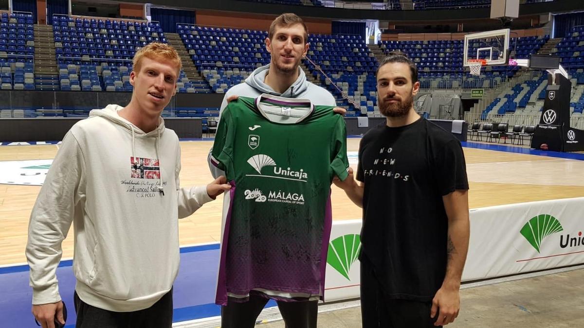 Alberto Díaz, Rubén Guerrero y Francis Alonso con la camiseta del sorteo firmada por la plantilla de Unicaja.