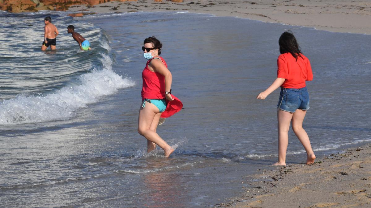 Una mujer se baña en una playa de A Coruña con la mascarilla puesta. / Víctor Echave