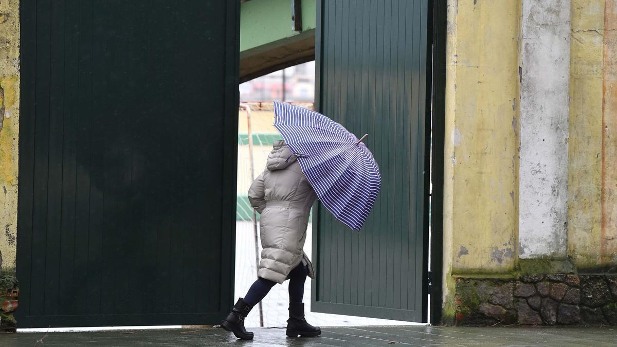Una persona camina, con paraguas, por el paseo de A Coruña en la zona de Riazor.