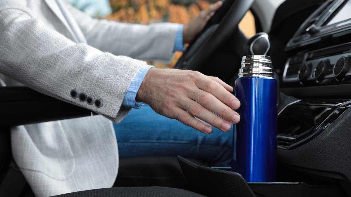 Un hombre acude a la oficina en coche con un termo con café.