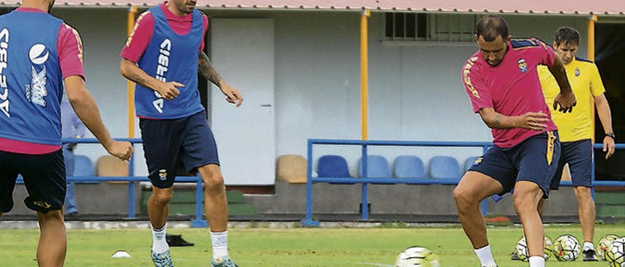 Nauzet Alemán da un pase en el entrenamiento de ayer en Barranco Seco ante Momo y David García.