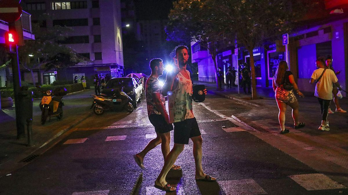 Varios jóvenes caminan por la zona de la plaza de Honduras de València antes de la entrada en vigor del toque de queda.   GERMÁN CABALLERO