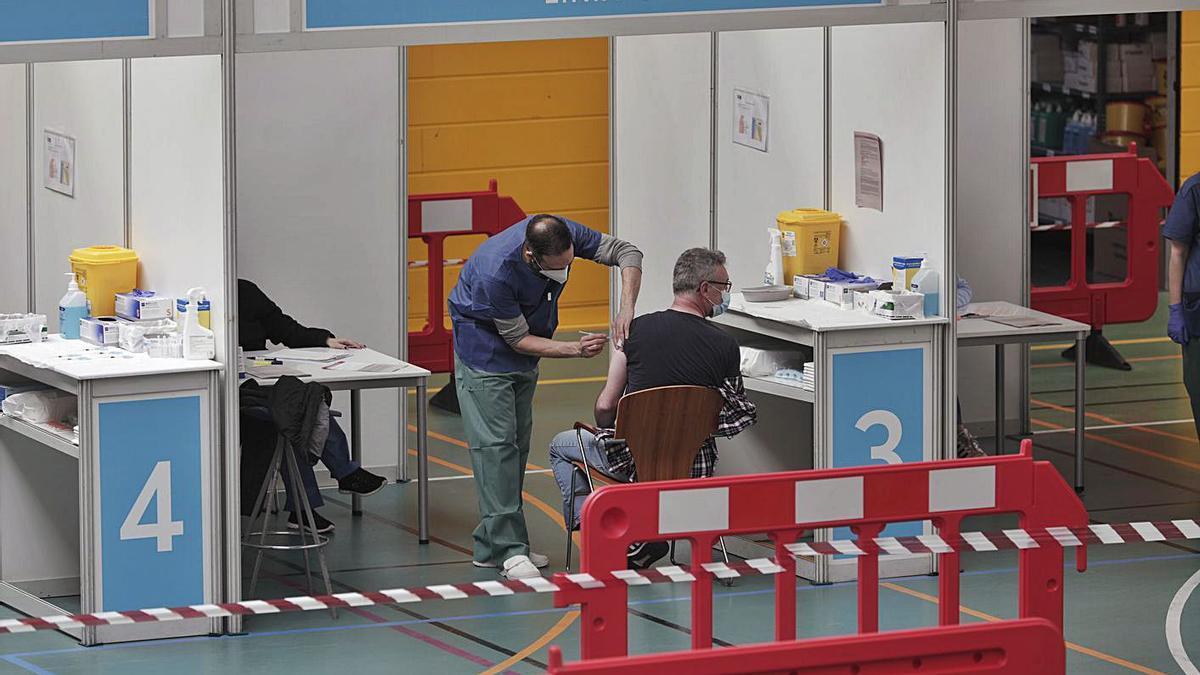 Un sanitario administrando vacunas en el polideportivo German Escalas.