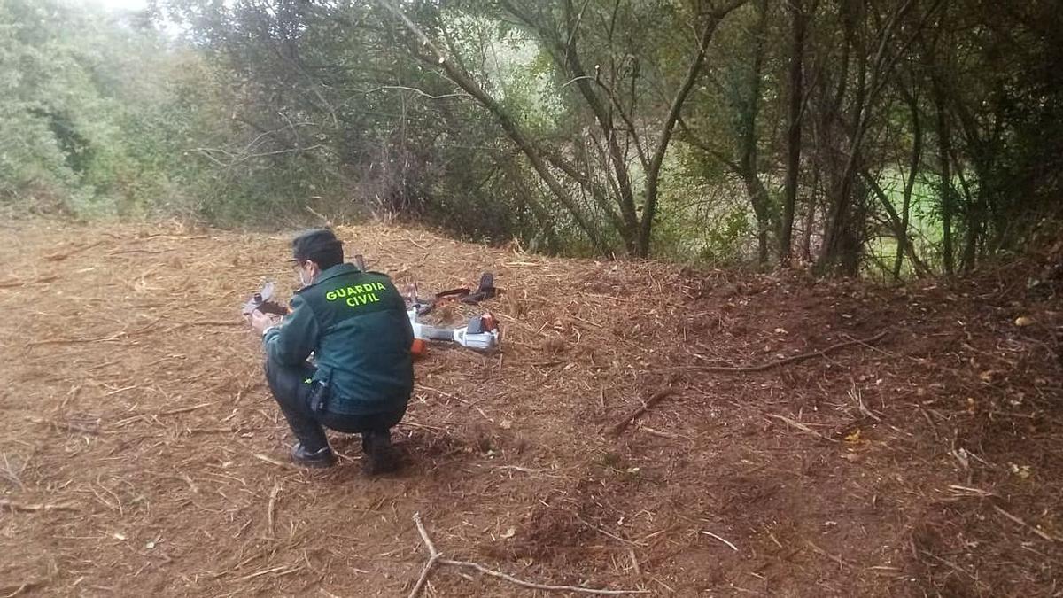 Un agente de la Guardia Civil, con la desbrozadora con la que trabajaba el fallecido.   | // GC