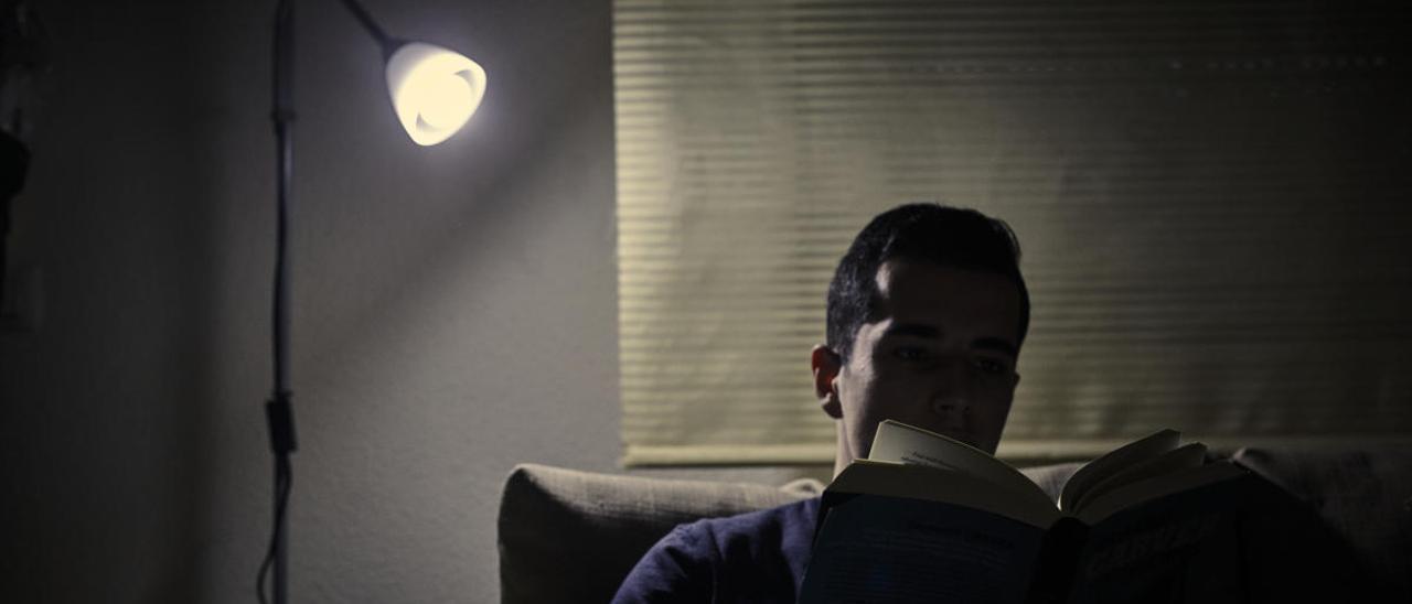 Un hombre lee un libro a la luz de una bombilla