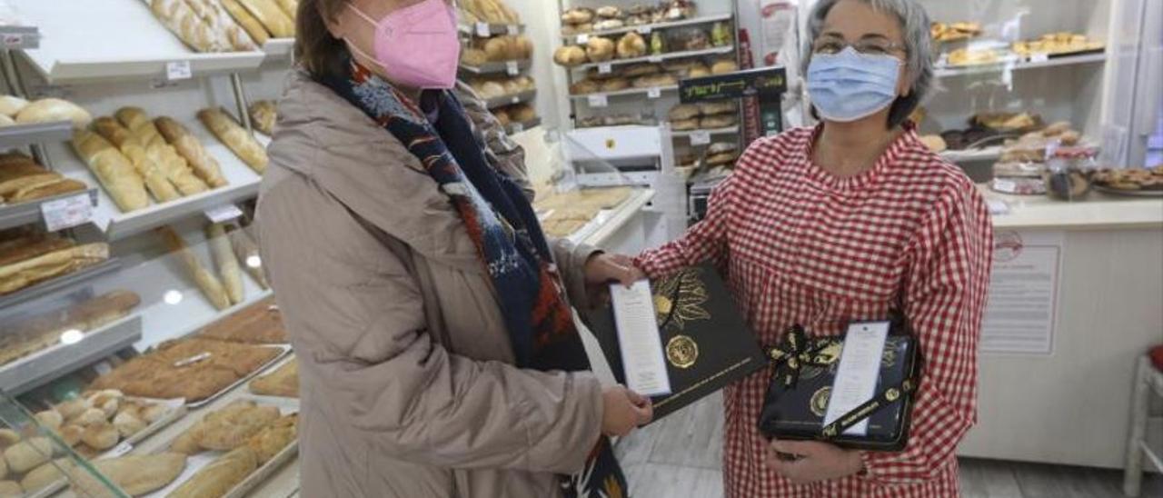 Margot Rodríguez entrega los marcapáginas a Emi García.