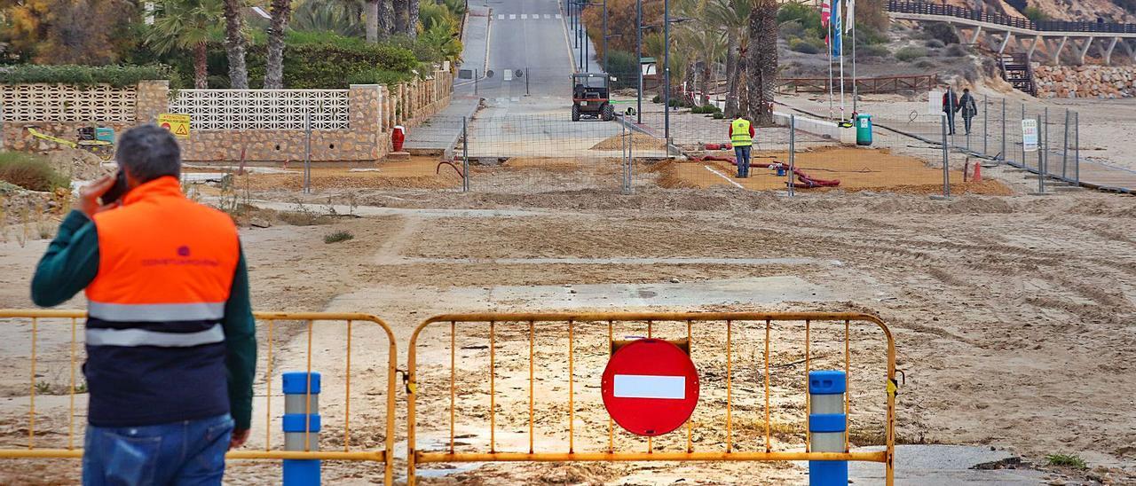 Vial cortado que divide en dos la avenida de las Adelfas donde, bajo la arena, se pueden ver restos del pavimento de la carretera.  | TONY SEVILLA