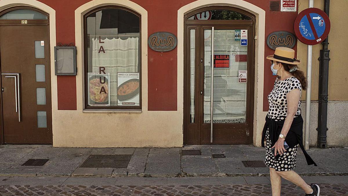Una mujer pasa por delante de un restaurante que ha echado el cierre. | Emilio Fraile