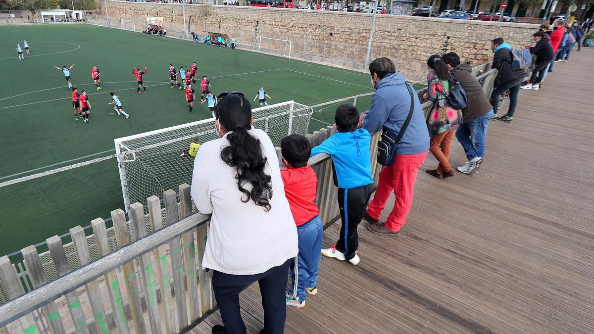 Padres y madres ven un partido de fútbol base desde un puente