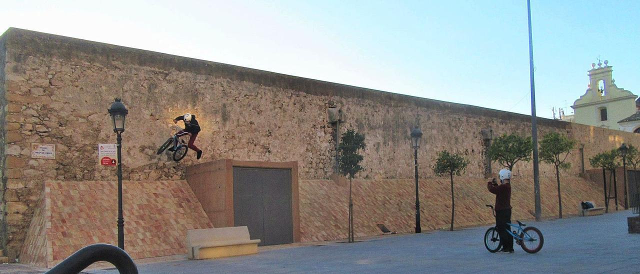 Un ciclista aprovecha la pirámide del contrafuerte para cicular con su bici por el muro del monumento, mientras otro lo graba.   L-EMV