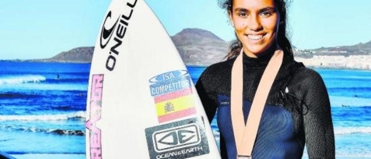 Lucía Machado posa en la Playa de La Cícer con su tabla y con la medalla conseguida en California.