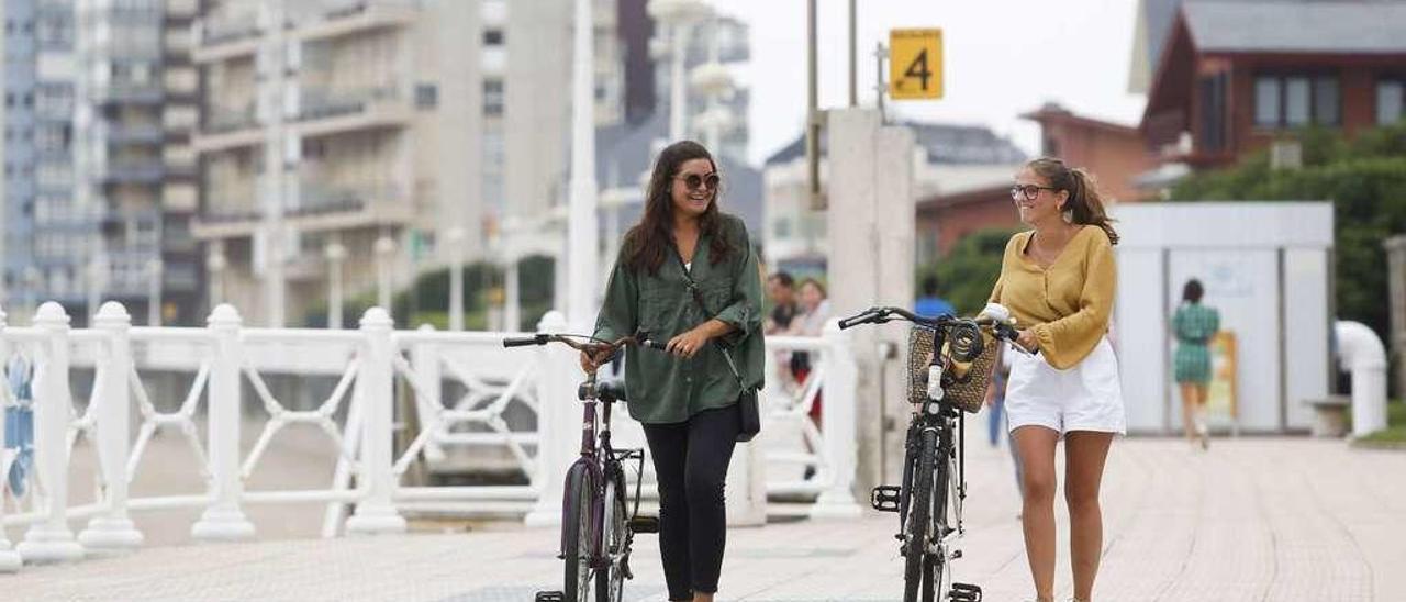Alicia Azpiroz y Lucía Forcada llevan sus bicicletas en la mano por el paseo de la playa de Salinas