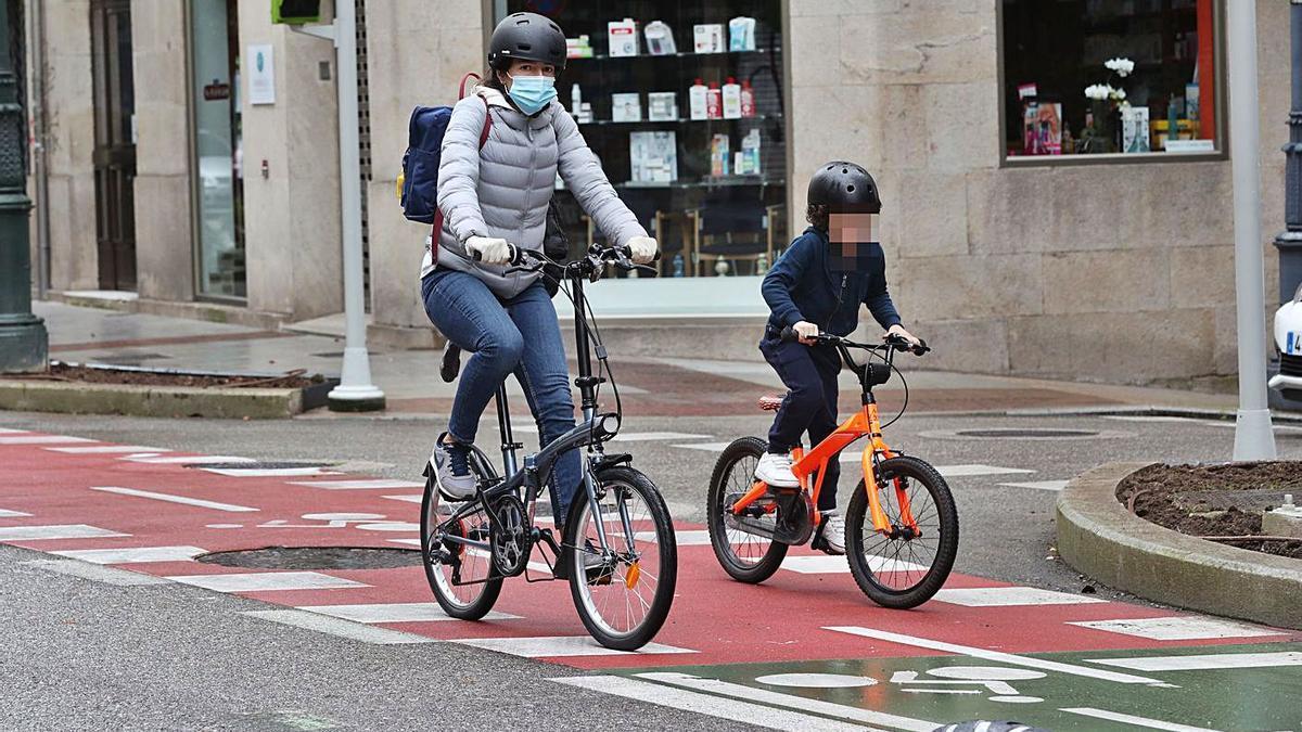 Una madre y su hijo circulan en bici, en Vigo.     // RICARDO GROBAS