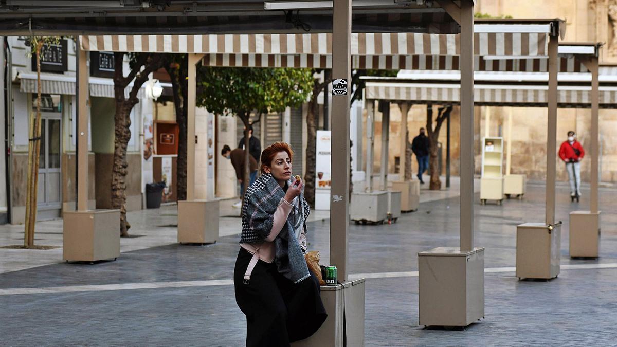 Una mujer se come unaempanadilla, ayer en laPlaza del Cardenal Belluga,en Murcia.