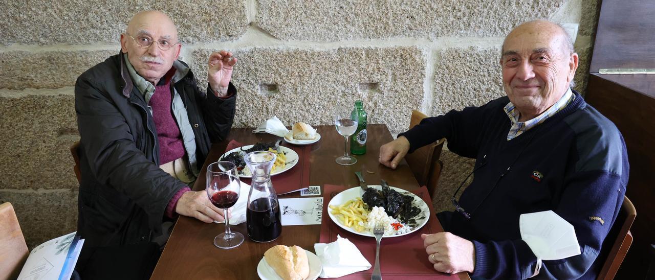 Dos personas degustan el choco en su tinta con arroz, ayer, en un restaurante de Redondela. / Alba Villar