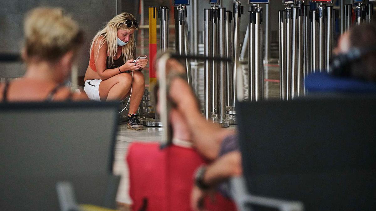 Una turista observa la pantalla de su móvil en el aeropuerto de Tenerife-Sur.     E.D.