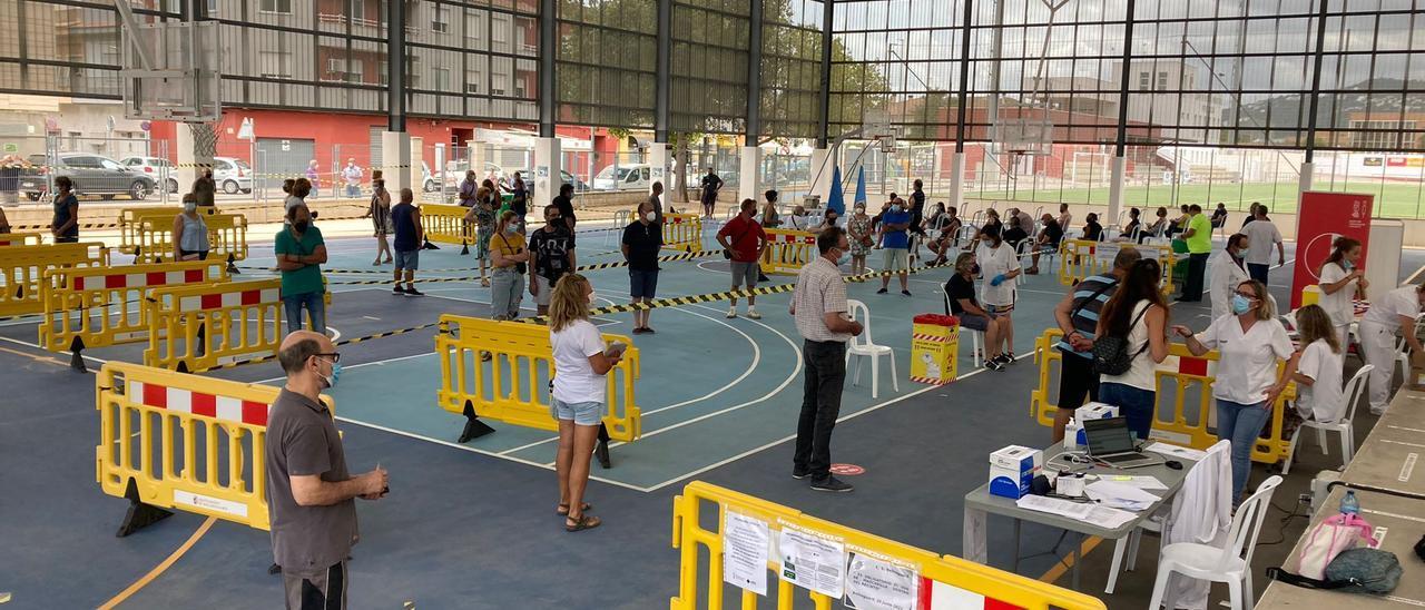 Decenas de personas esperan o son vacunadas en el pabellón polideportivo de Bellreguard.