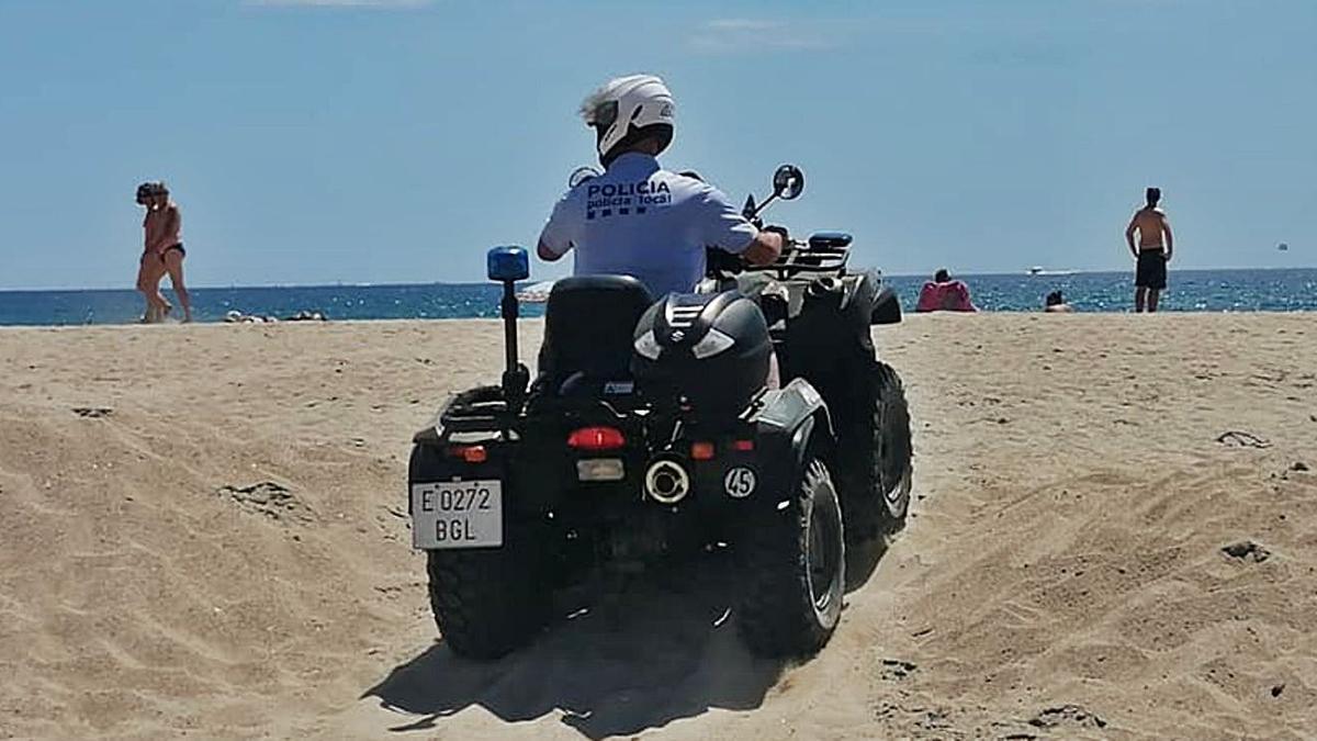 Un agent de la Policia Local, fent un servei a la platja conduint un quad
