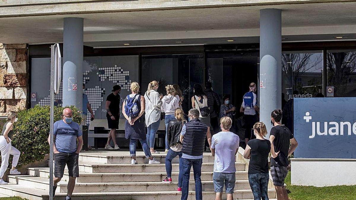 Turistas haciendo cola en la Clínica Juaneda de Muro esperando que les hagan la prueba covid. | B. RAMON