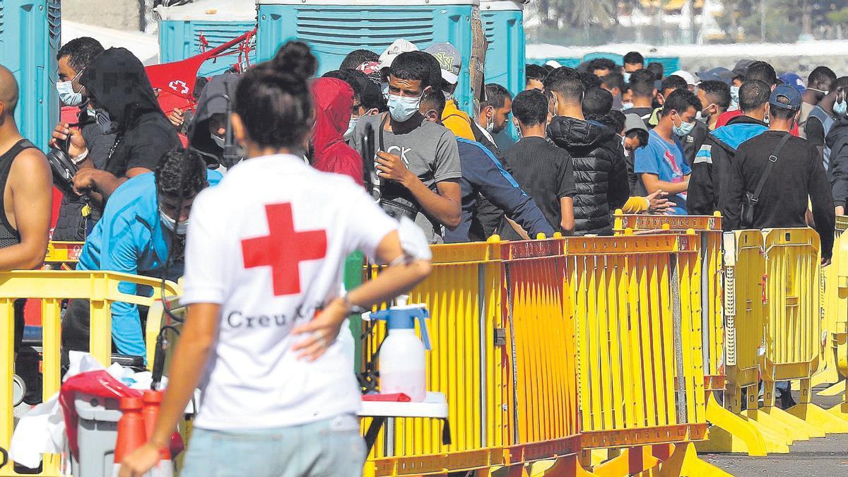 Una voluntaria de la Cruz Roja junto a un grupo de migrantes.