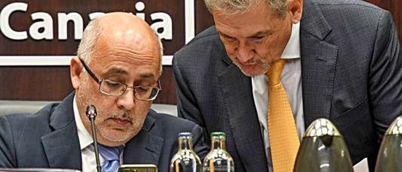 Antonio Morales y Pedro Justo Brito consultan un teléfono móvil durante en Debate del Estado de la Isla.