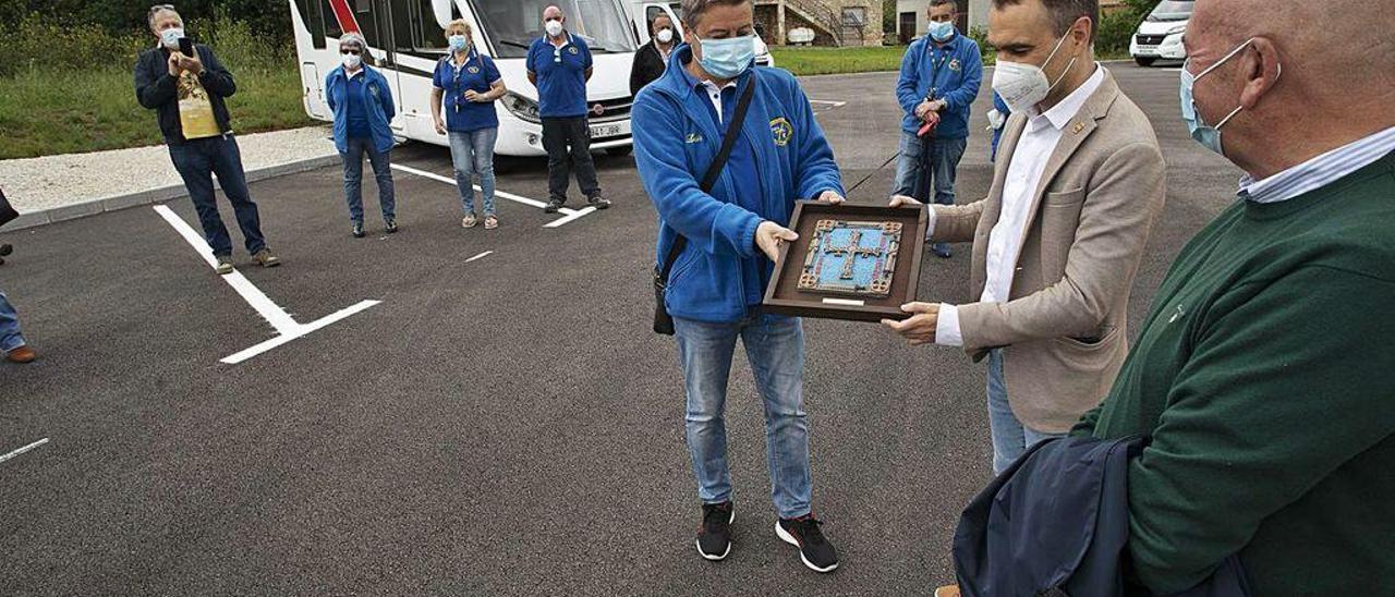 José Luis Villanueva entrega un escudo de Asturias al alcalde, Iván Fernández, como agradecimiento a la apertura del nuevo estacionamiento de autocaravanas, ayer, en Overo.