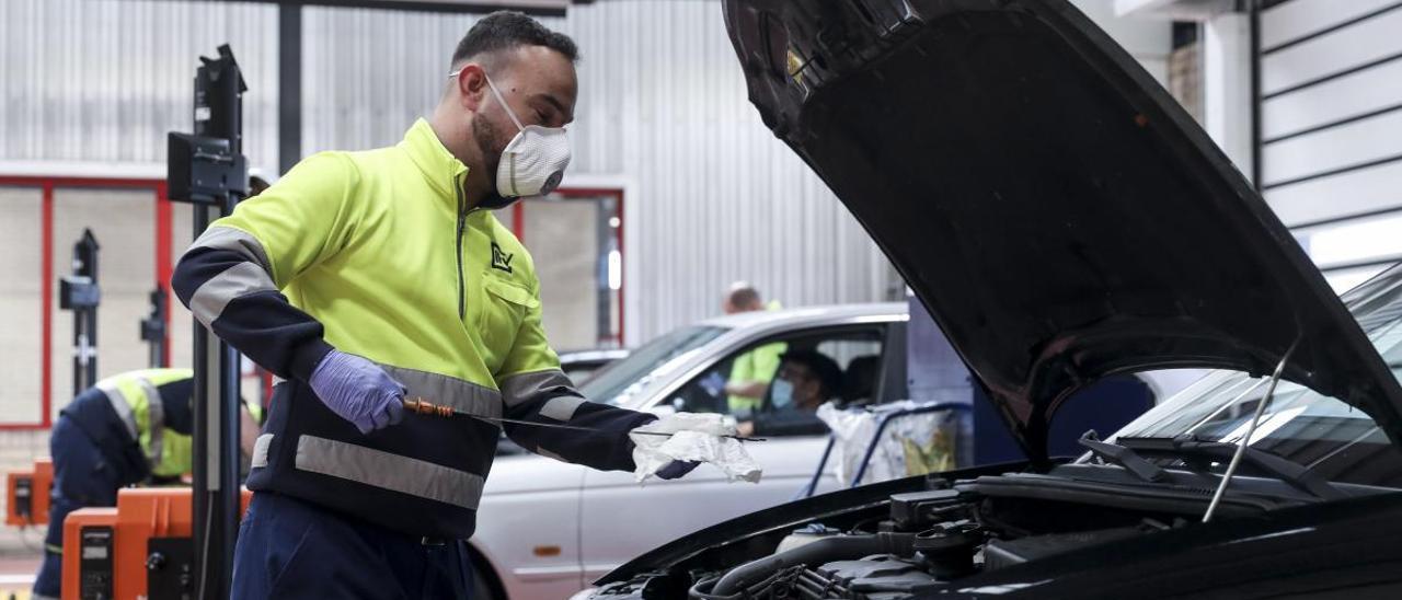 Un operario de la ITV de Gijón comprueba el nivel de aceite de un vehículo.