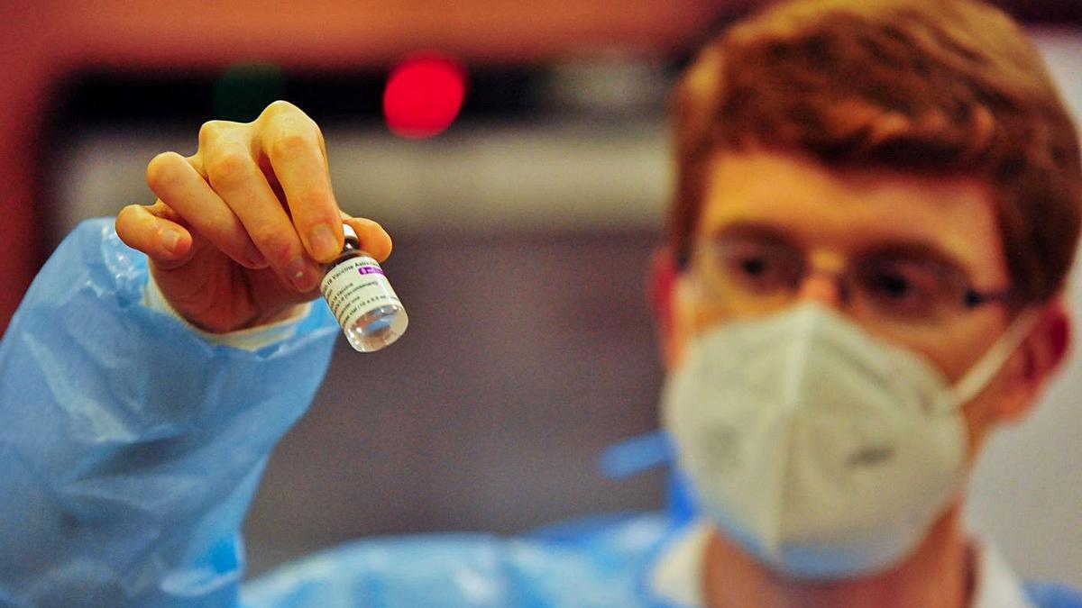 Un sanitario con una vacuna de AstraZeneca en la mano, en Vilagarcía.     // IÑAKI ABELLA