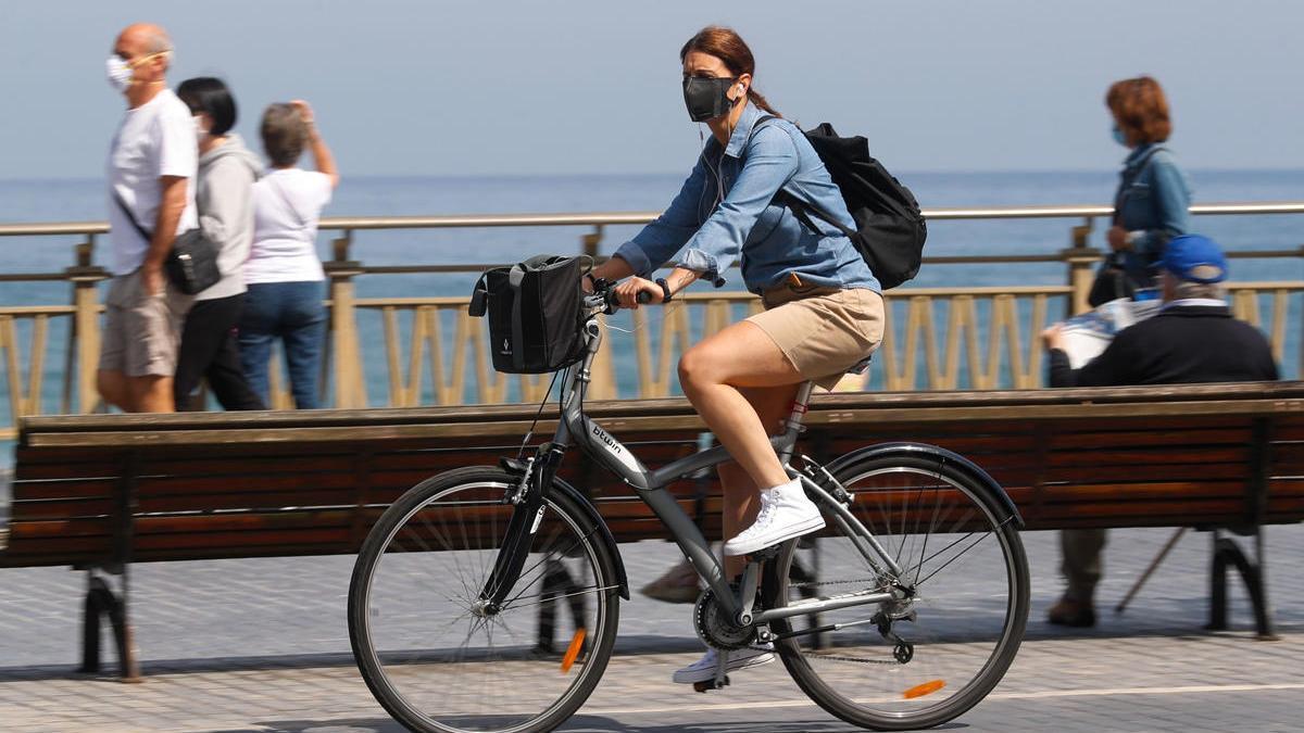 Una mujer pasea en bicicleta protegida con una mascarilla por el paseo de la Zurriola de San Sebastián.