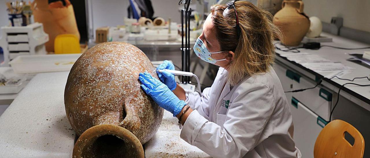 Una restauradora trabaja en una de las ánforas recuperadas en Formentera.   MAEF