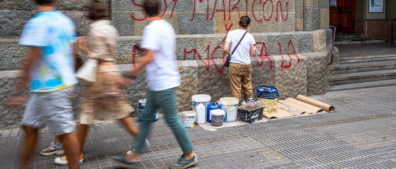 Un operario borra una pintada con la letra de 'Maricón', de Samantha Hudson, en la parroquia en Barcelona.