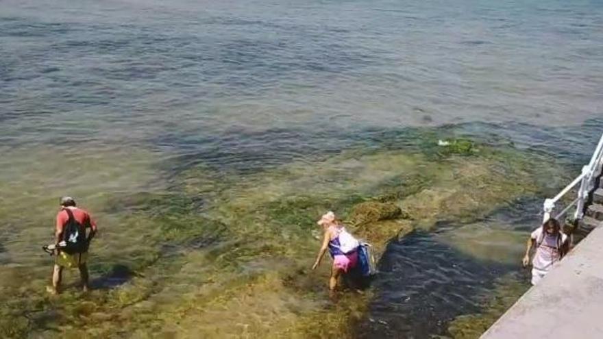Pillan a varios bañistas colándose por el mar en la playa de San Lorenzo cerrada por exceso de aforo