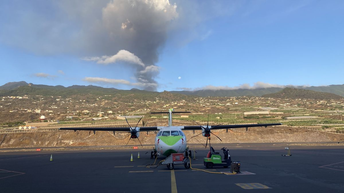 A Binter plane on the La Palma airport runway, with the erupting volcano in the background