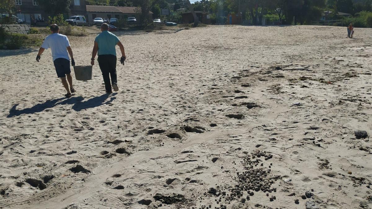 Personal de la empresa concesionaria, retirando esta mañana los restos de fecales de la arena. / G.N.