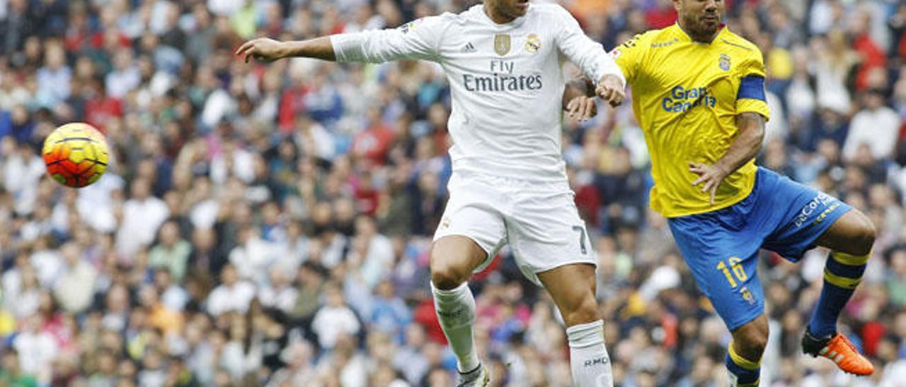 El central y capitán de la UD Aythami Artiles despeja el balón, ante el delantero y goleador ayer del Madrid, Cristiano Ronaldo, en el Santiago Bernabéu.