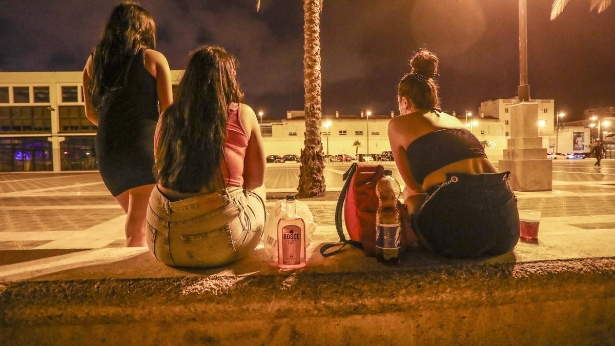 Tres jóvenes beben el viernes por la noche en la playa.