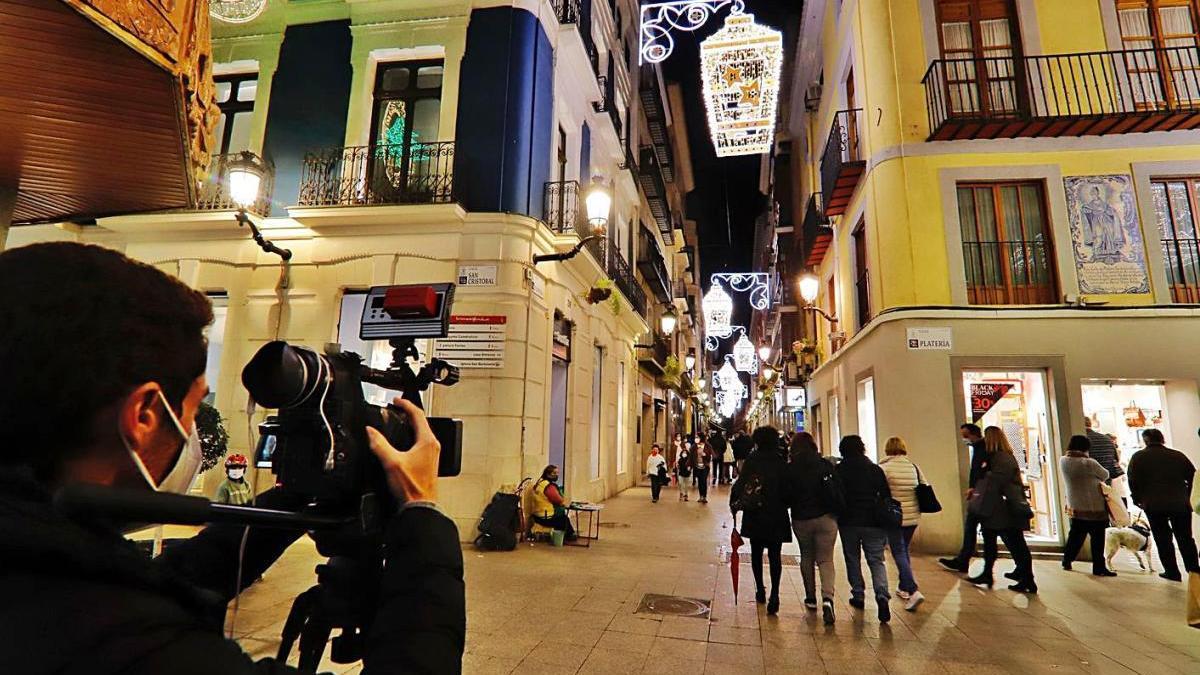 Un cámara toma imágenes de una calle del centro de Murcia decorado por Navidad.