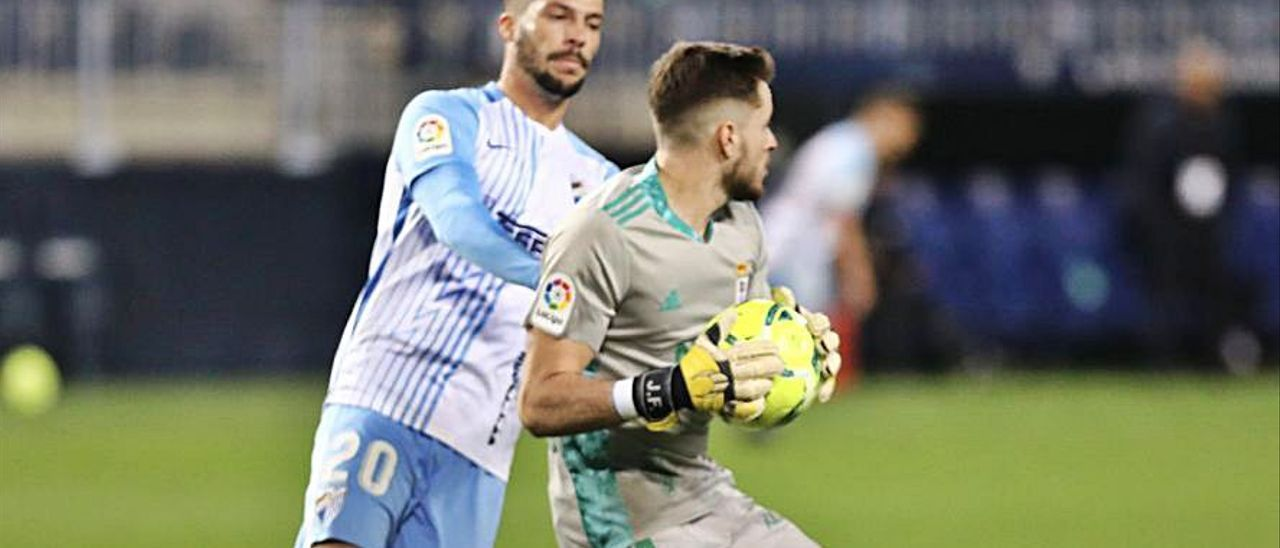 Femenías, con el balón, presionado por Caye Quintana, del Málaga.