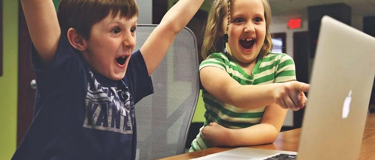 Dos alumnos celebran sus  logros ante una pantalla.    // FDV