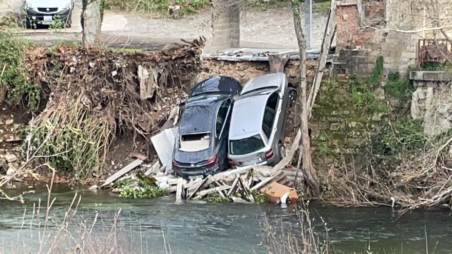 Susto en Valdés al caer dos coches al río por el desplome de un garaje