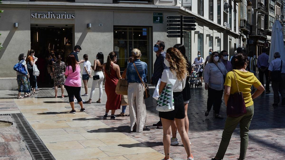 Colas de malagueños esperando para entrar en una tienda de ropa mientras se respetan las medidas de seguridad.