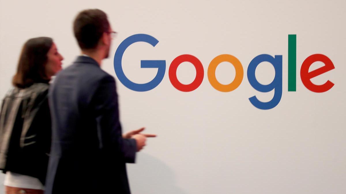 Dos personas observan el logo del Google.
