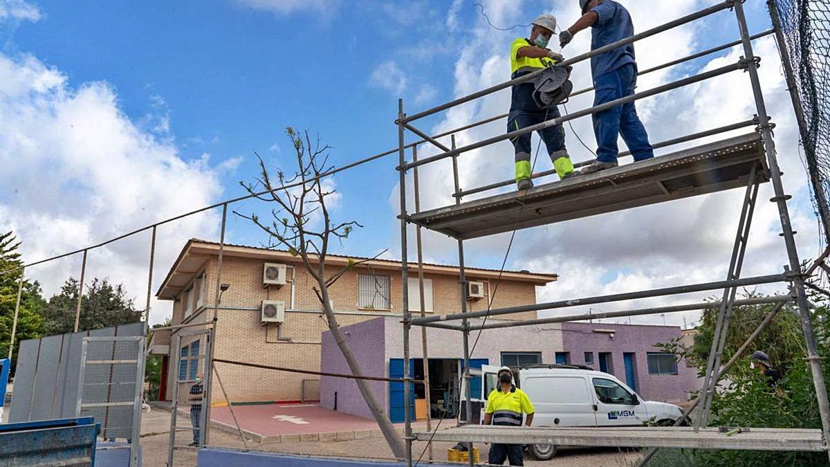 Operarios reparan la valla de un colegio. | A.C.