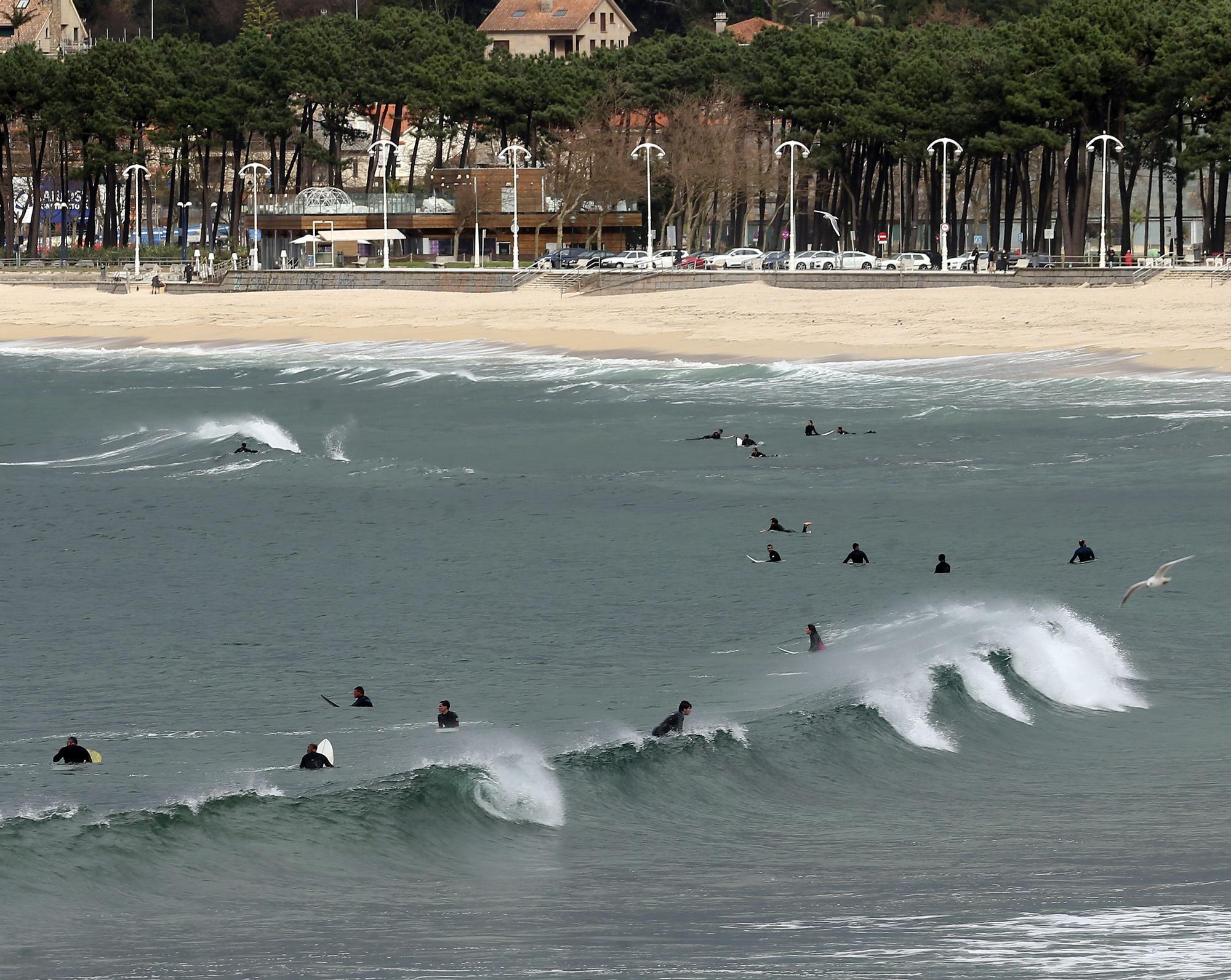 Surfistas practicando junto a la desembocadura del río Lagares y la playa de Samil