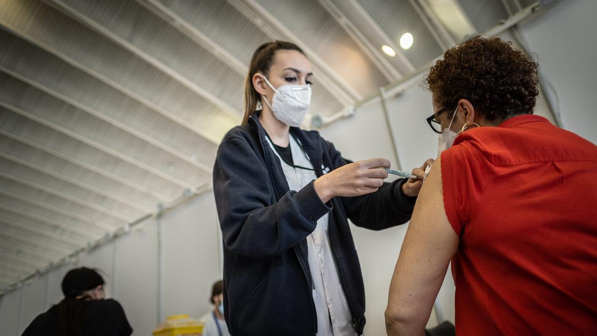 Una mujer se vacuna contra la covid en el Recinto Ferial de Tenerife.