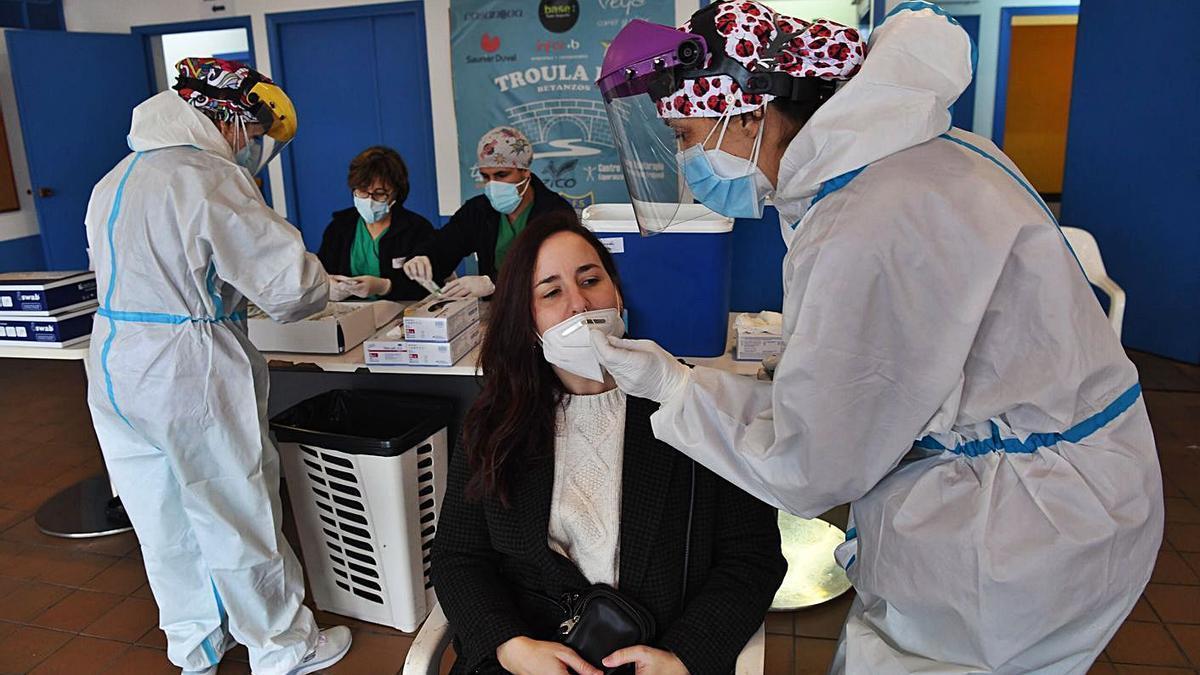 Una enfermera extrae una muestra a una joven durante el cribado poblacional que arrancó ayer en Betanzos, y que se prolongará durante varios días. | L. O.