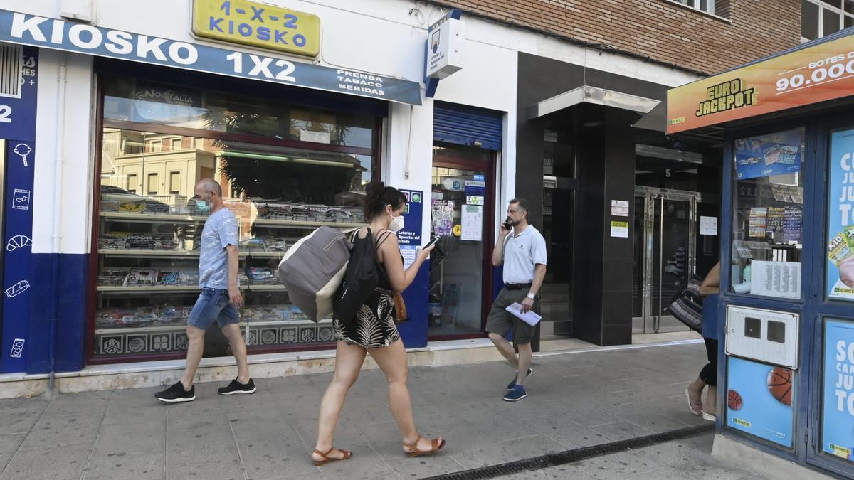 Viandantes pasan frente al escaparate de un kiosco del centro de Castelló.