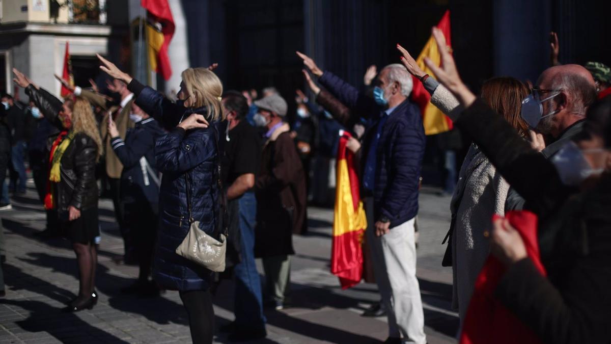 Varias personas sostienen banderas de España y levantan el brazo derecho durante una concentración en conmemoración de la muerte de Franco y de José Antonio Primo de Rivera en la Plaza de Oriente, en Madrid.
